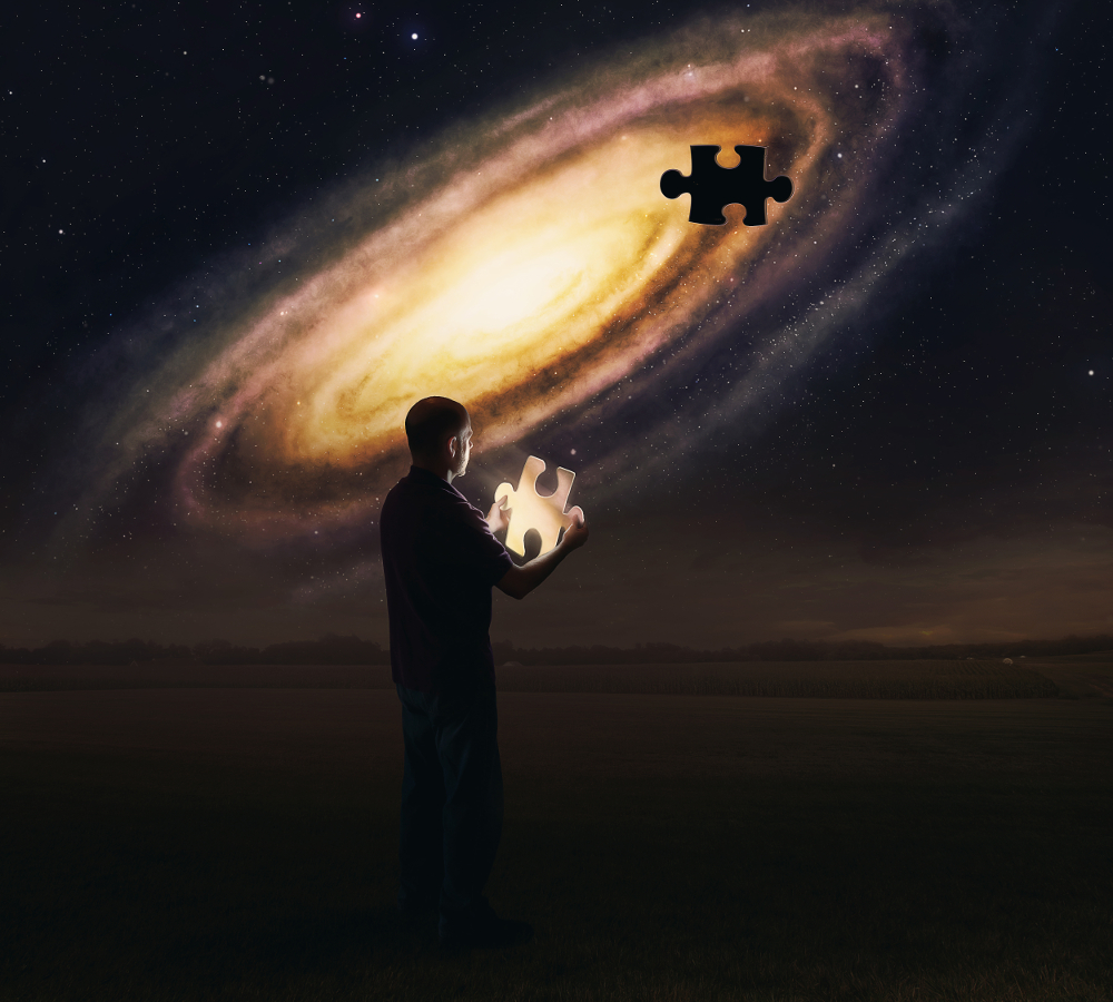 A man holds a glowing puzzle piece from the galaxy.